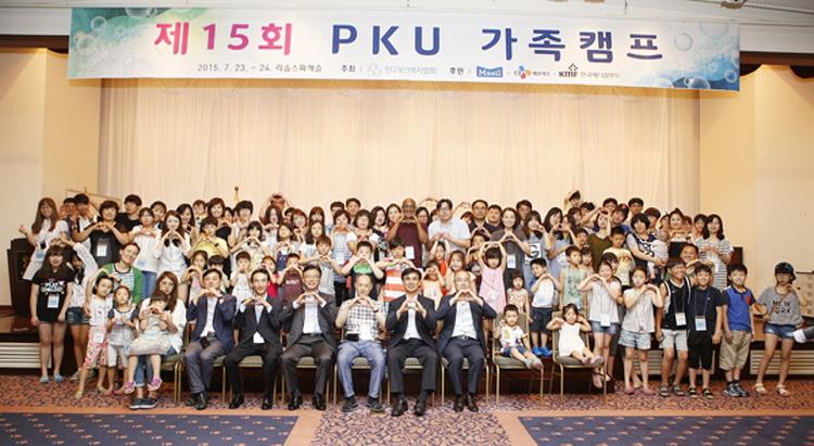 CJ제일제당이 참여한 제15회 PKU 가족캠프 행사 단체 사진으로, 이 행사에 참여한 관계자와 PKU 환우 가족들이 모여 손으로 하드 모양을 만들며, 포즈를 취하고 있다.