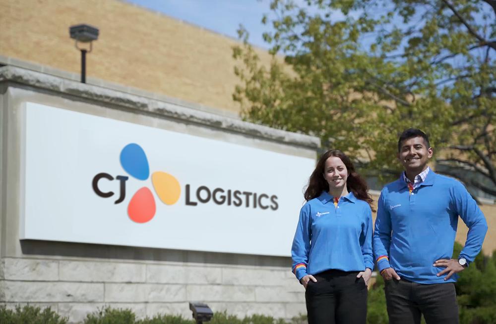 'CJ Logistics'로 브랜드가 통합된 CJ대한통운 미 통합법인의 현판 앞에서 파란색 유니폼을 입은 직원들이 기념촬영을 하고 있다.