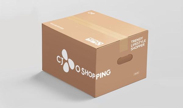 CJ오쇼핑의 착한 손잡이 배송 박스 모습으로, 테이핑 된 박스 옆에 영문으로 CJ오쇼핑 로고가 삽입되어 있고, 양쪽 부분에 손을 넣을 수 있는 구멍이 뚫려 있다.