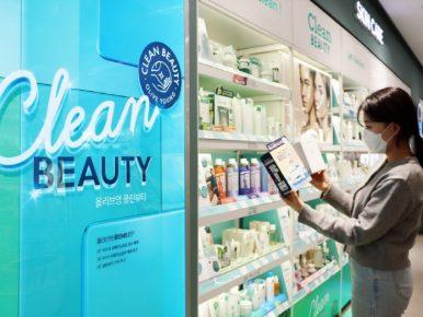 올리브영 명동 플래그십을 방문한 고객이 클린뷰티 제품을 살펴보고 있는 모습으로, 마스크를 낀 채로 두 제품을 손에 들고 제품을 확인하고 있다.