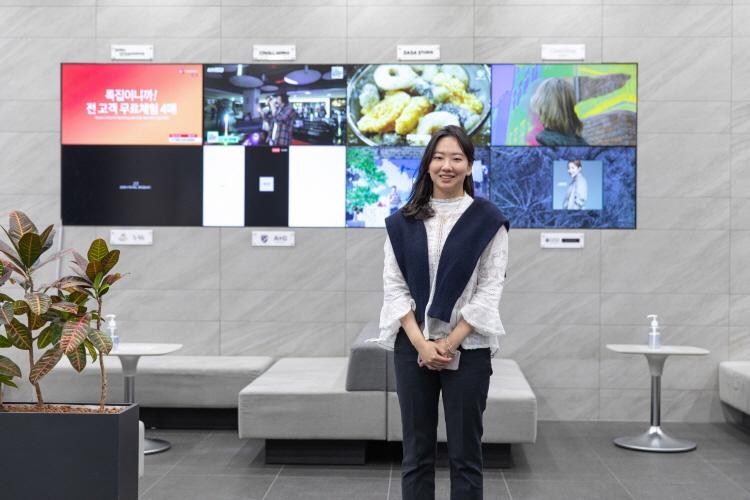 안혜성MD가 홈쇼핑이 방영되는 모니터가 늘어선 벽을 배경으로 포즈를 잡고 카메라를 응시하고 있다.