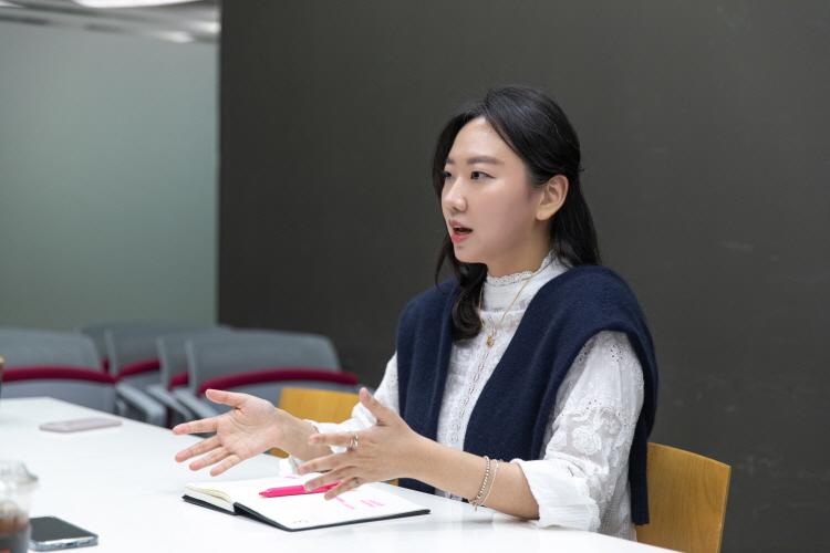 안혜성PD가 회의실에 앉아 이야기하는 모습. 손으로 제스처를 취하며 설명하고 있다.