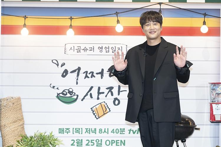 tvN 예능 '어쩌다 사장' 제작보고회 겸 개업식 현장에 검은 정장 차림으로 온 차태현이 두 손을 활짝펴 인사하는 모습으로, 카메라를 향해 포즈를 취하고 있다.