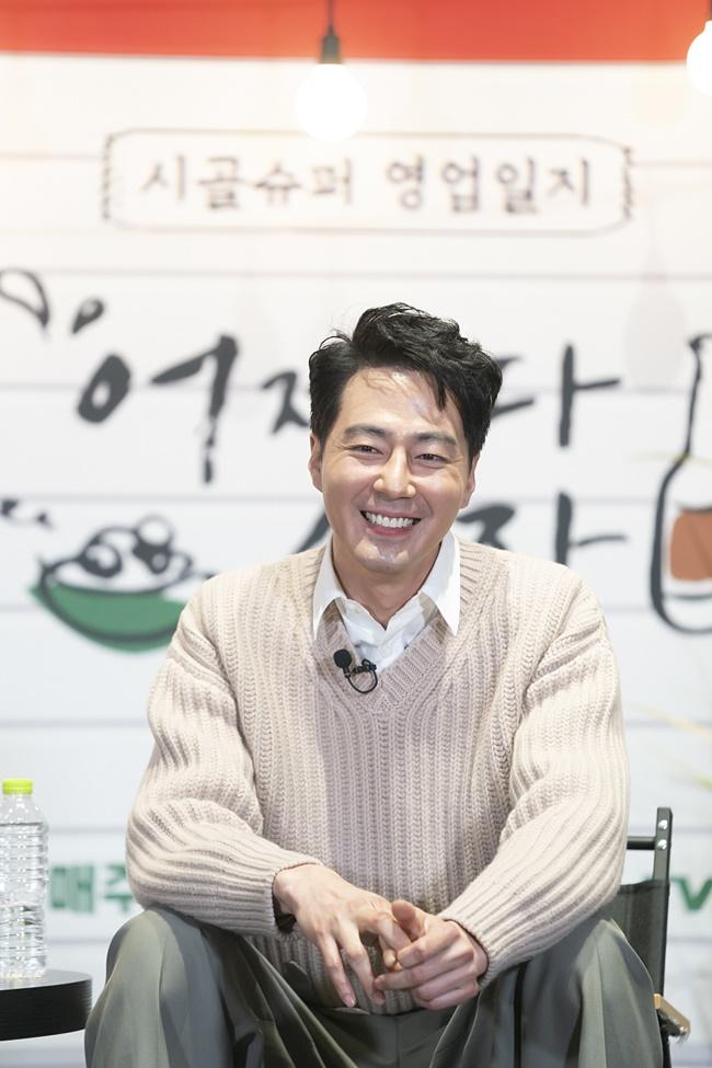 tvN 예능 '어쩌다 사장' 제작보고회 겸 개업식 현장의 모습으로, 의자에 앉은 조인성이 미소를 짓고 있다.
