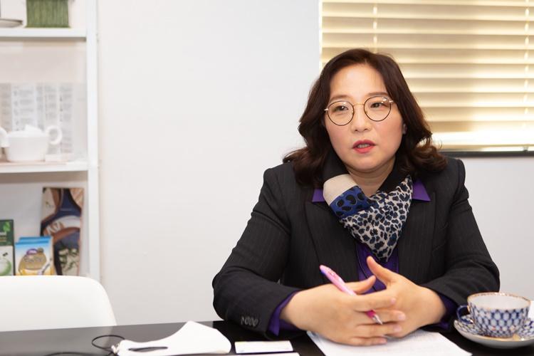 유웰데코의 김정희 대표가 회의실에 앉아 이야기하고 있는 모습. 손에는 펜을 들고 있고, 책상 위에는 종이와 명함이 놓여있다.