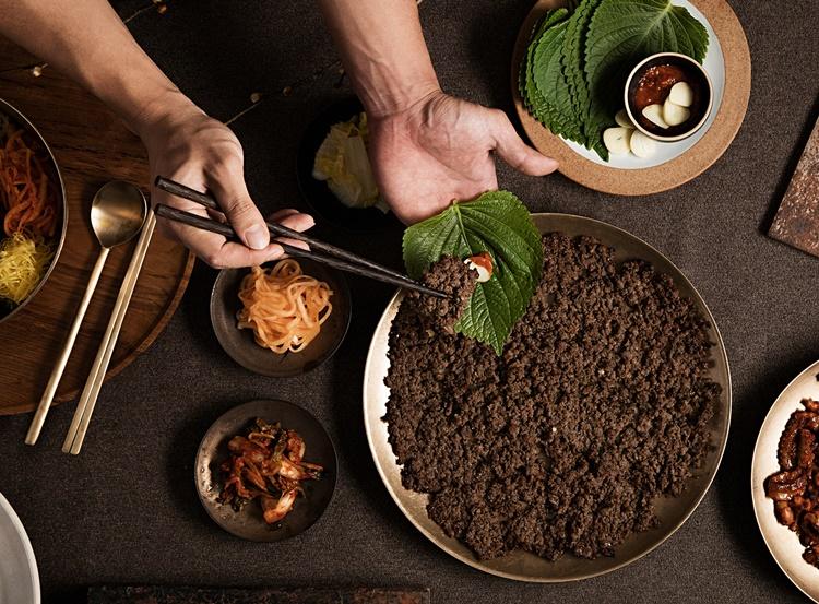 역전회관의 바싹 불고기가 접시에 놓여있고, 이미지 상단에는 깻잎, 마늘과 바싹불고기를 싸먹는 손이 있다. 바싹불고기 접시 주변으로는 무생채, 깻잎, 쌈장, 등의 반찬이 놓여있다.