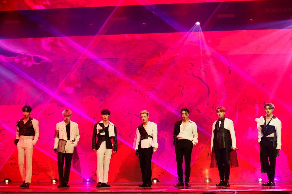 '케이콘택트3'에서 도쿄를 배경으로 온라인 월드투어 공연을 펼친 ATEEZ 멤버들이 붉은색 조명 아래 포즈를 취하고 있다.