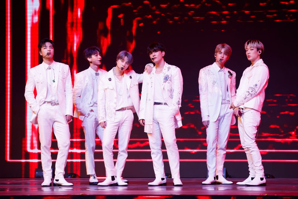 '케이콘택트3'에서 붉은색 조명이 눈에 띄는 무대에서 iKON의 여섯 멤버가 포즈를 취하고 있다.