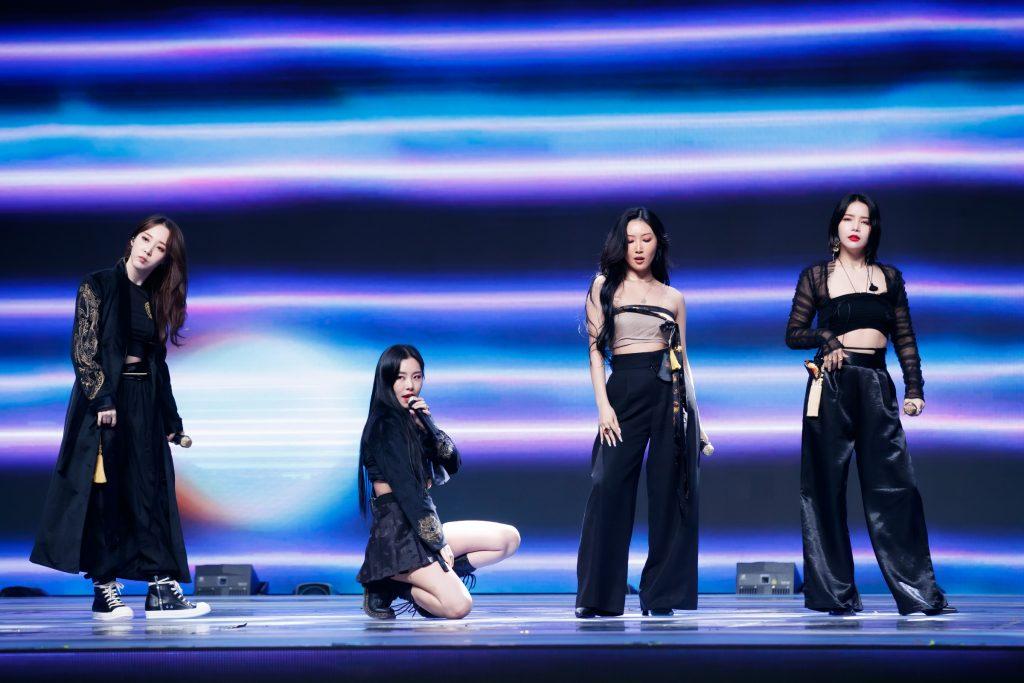 '케이콘택트3'에서 우리나라 전통 한복을 입고 방콕 온라인 월드투어를 진행한 마마무의 모습으로, 휘인을 제외한 세 멤버는 서서 곡에 맞는 안무를 보여주고 있다.