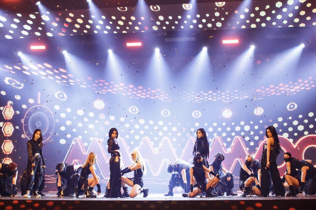 '케이콘택트3'에서 우리나라 전통 한복을 입고 방콕 온라인 월드투어를 진행한 마마무의 모습으로, 복면을 쓴 백댄서들은 앉아 있고, 네 멤버는 서서 카메라를 보고 있다.