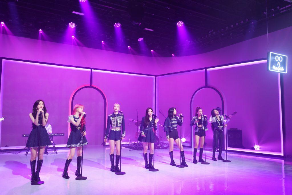 '케이콘택트3'에서 제복 의상을 뽐내며 완벽한 LA 무대를 장식한 오마이걸 7멤버 모두 스탠드 마이크를 잡고 자신들의 노래를 부르고 있다.