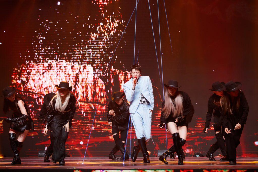 '케이콘택트3'에서 섬세한 춤사위로 LA 무대를 가득 채운 WOODZ(조승연)의 모습으로 하늘색 슈트를 입은 채 검은색 무대의상을 입은 여성 백댄서들과 함께 곡에 맞는 안무를 보여주고 있다.