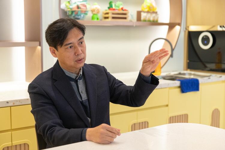 홍민호 님이 테이블에 앉아 키즈 식자재 영업에 대해 설명하는 모습. 왼손을 높이 드는 제스처를 취하고 있다.