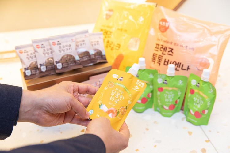 키즈 식자재, 아이들 간식으로 사용되고 있는 쿠키, 비엔나 소시지, 음료 등이 나열돼 있고, 손으로 '마시는 달콤한 하루'라는 음료를 들어 보이는 모습.