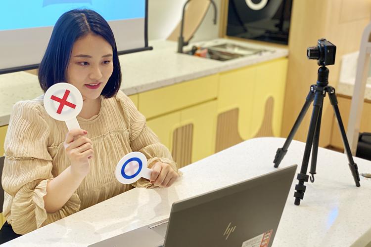 코로나19로 인해 비대면으로 진행되는 모습.  OX 푯말을 양 손에 든 선생님이 앉아있고, 앞에는 노트북이, 오른쪽에는 카메라가 놓여있다.