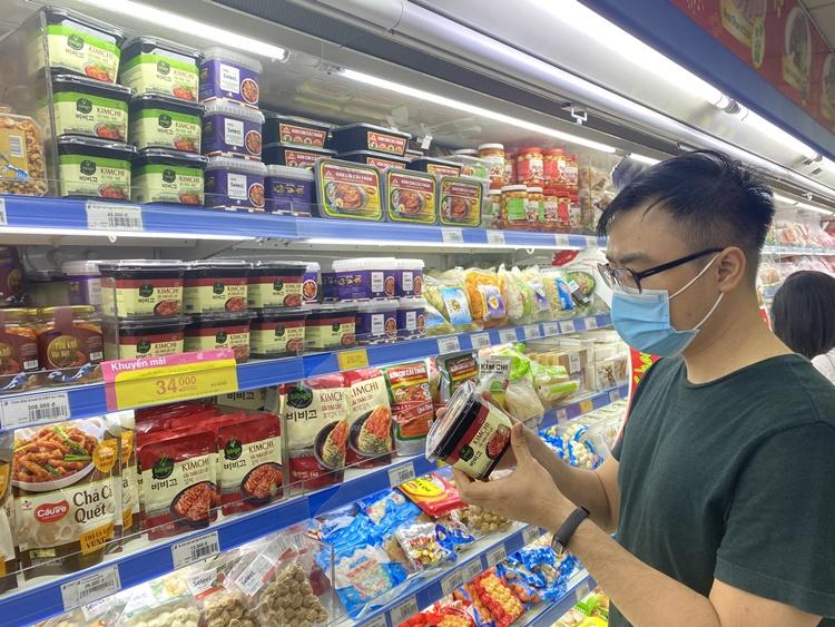 대형 마트에서 비비고 김치를 살펴보고 있는 남성 소비자의 모습. 왼쪽에 있는 진열대에는 김치를 비롯한 식재료가 진열돼 있고, 한 남성이 비비고 김치 패키지를 들고 살펴보고 있다.