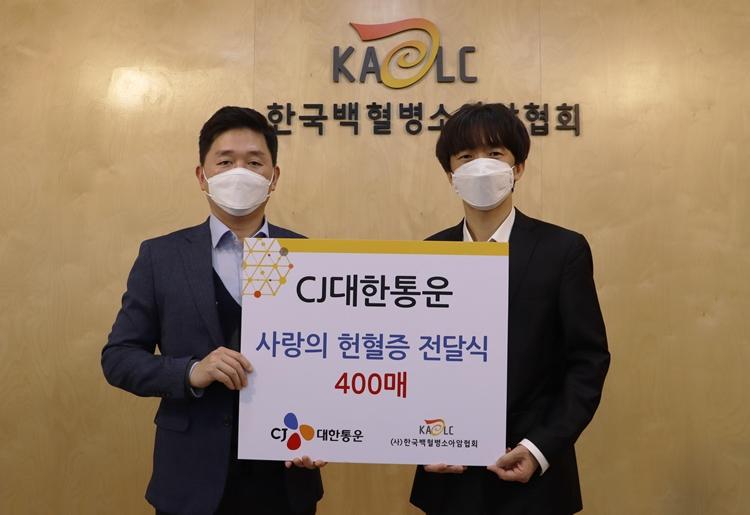 왼쪽에 있는 CJ대한통운 박진규 부장과 오른쪽 한국백혈병소아협회 서용화 과장이 한국백혈병소아암협회 로고 앞에 CJ대한통운 사랑의 헌혈증 전달식 400매라고 적힌 판을 함께 들고 서있는 모습.