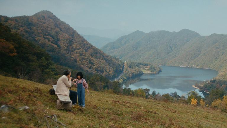 영화 '정말 먼 곳' 스틸로, 강원도 화천의 아름다운 풍경 아래로 농장주 중만의 어머니 명순(최금순)과 즐거운 한 순간을 보내는 진우의 딸, 설(김시하)의 모습이 보인다.