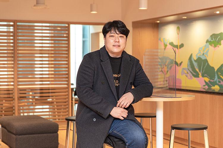 공유주방 플랫폼 '나누다키친'을 론칭한 위대한상사 김유구 대표가 회사 사무실 의자에 앉아 테이블에 왼팔을 기대어 카메라를 향해 포즈를 취하고 있다.