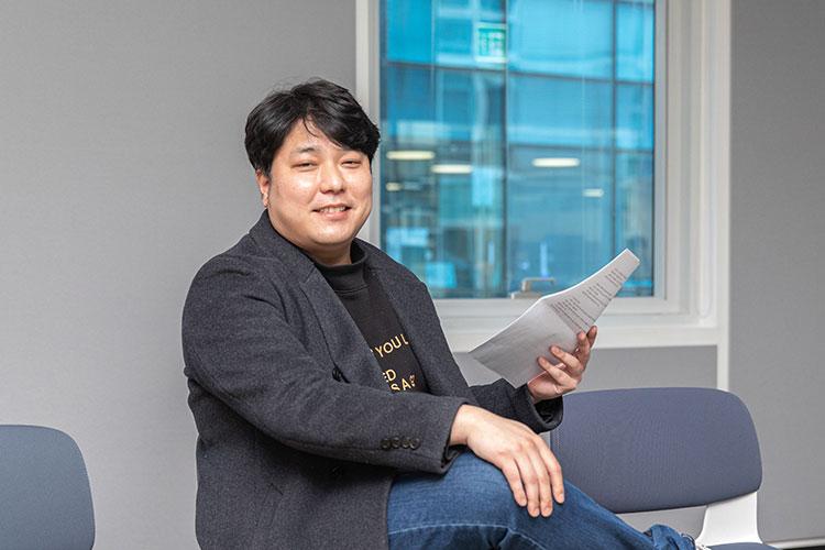 공유주방 플랫폼 '나누다키친'을 론칭한 위대한상사 김유구 대표가 회사 회의실 의자에 앉아 왼손에는 회의 자료를 들고 카메라를 향해 포즈를 취하고 있다.