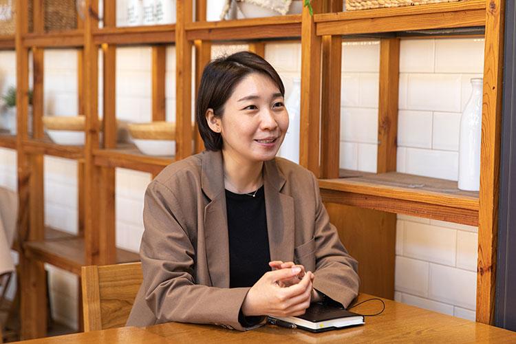 김성희 님이 나무 진열장을 배경으로 앉아 인터뷰하는 모습.