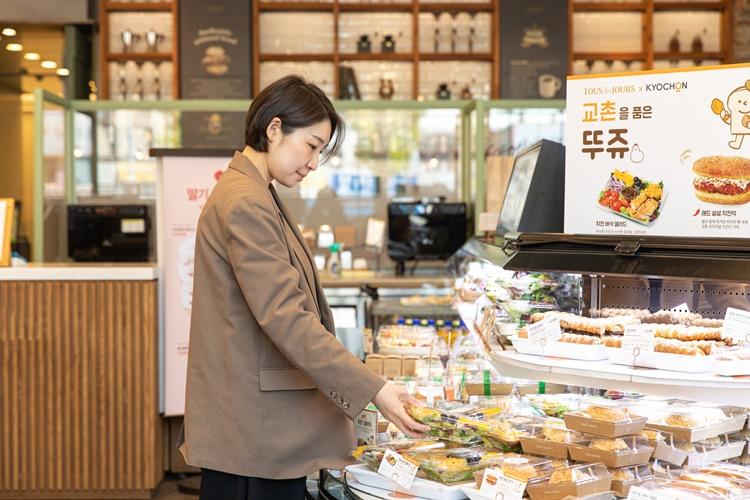 김성희 님이 교촌을 품은 뚜쥬 진열대에 놓인 제품을 오른 손으로 살짝 들어보며 상품을 체크하는 모습.