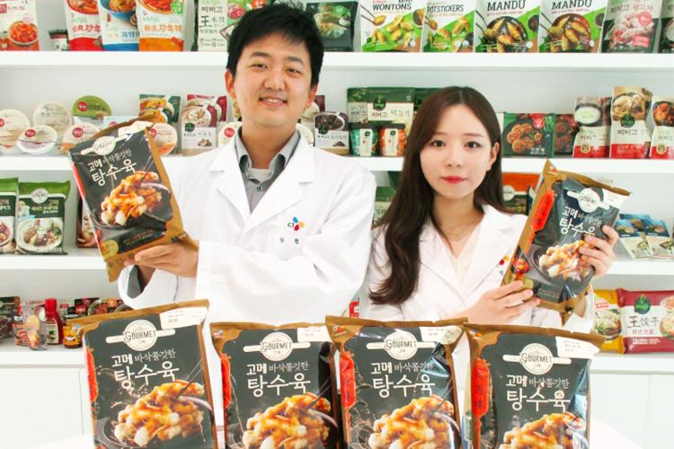 왼쪽부터 '고메 바삭쫄깃한 탕수육'을 만든 김현석 님과 박혜린 님이 고메 탕수육을 들고 카메라를 응시하고 있는 모습. 뒤에 놓인 선반에는 만두, 햇반, 김치 등의 제품이 진열돼 있다.
