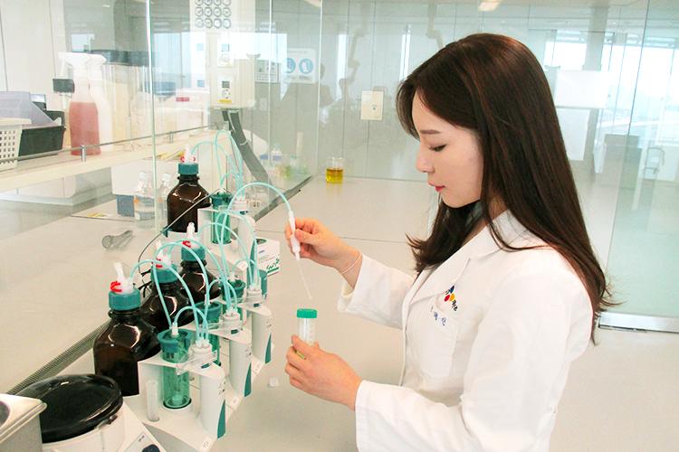 고메 탕수육 소스 개발을 담당한 박혜린 님의 모습. 연구실에서 기구를 들고 있다.