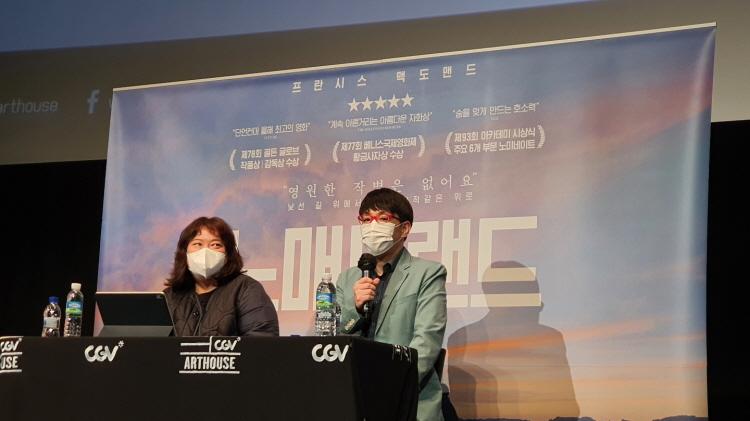 '이동진의 라이브톡' 100회 진행을 맡은 이다혜 기자(왼쪽)와 이동진 영화평론가(오른쪽)가 노매드랜드 현수막을 배경으로 테이블에 앉아 있다.