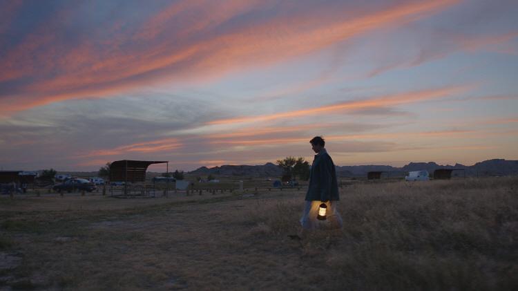 프란시스 맥도맨드 주연, 클로이 자오 연출 영화 '노매드랜드'의 스틸로 프란시스 맥도맨드가 랜턴을 들고 유목민들이 모여 사는곳으로 가고 있다.