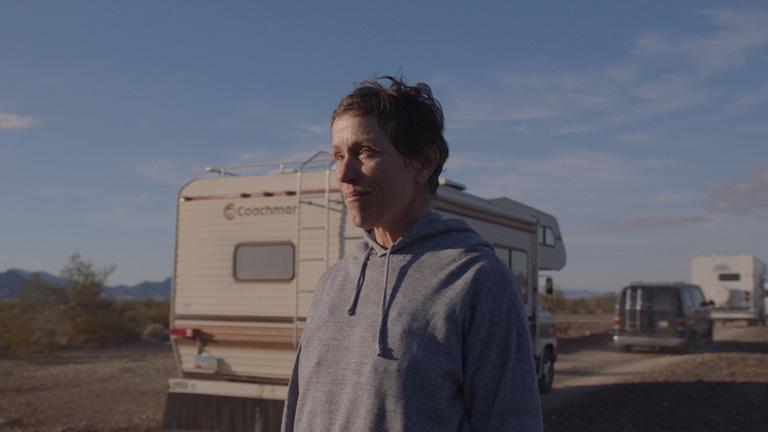 프란시스 맥도맨드 주연, 클로이 자오 연출 영화 '노매드랜드'의 스틸로 프란시스 맥도맨드가 차로 이동하는 유목민들을 물끄러미 쳐다보고 있다.