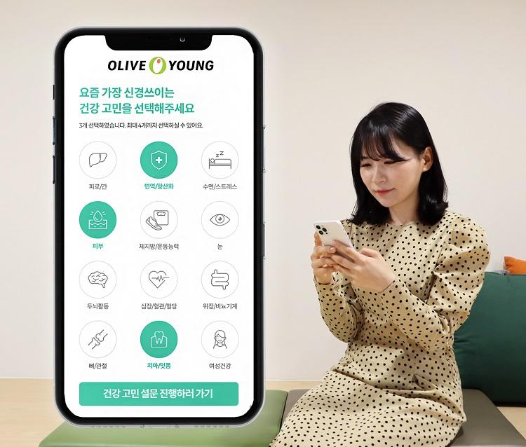 올리브영 모바일 앱을 통해 맞춤형 건강기능식품을 추천 받고 있는 MZ세대 이미지로, 왼쪽에는 스마트폰 내 올리브영 모바일 앱이 띄워져 있고, 오른쪽에는 이 화면을 보고 있는 MZ세대 여성이 소파에 앉아있다.