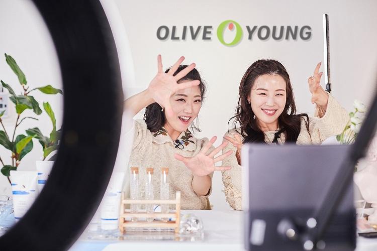 올리브영 명동 플래그십 내 디지털 스튜디오에서 '올라이브' 생방송을 진행하는 모습으로, 올리브영에서 판매하는 뷰티 제품을 테이블 위에 올려놓은 채 두 여성 크리에이터가 카메라를 향해 손을 활짝 펼치고 있다.
