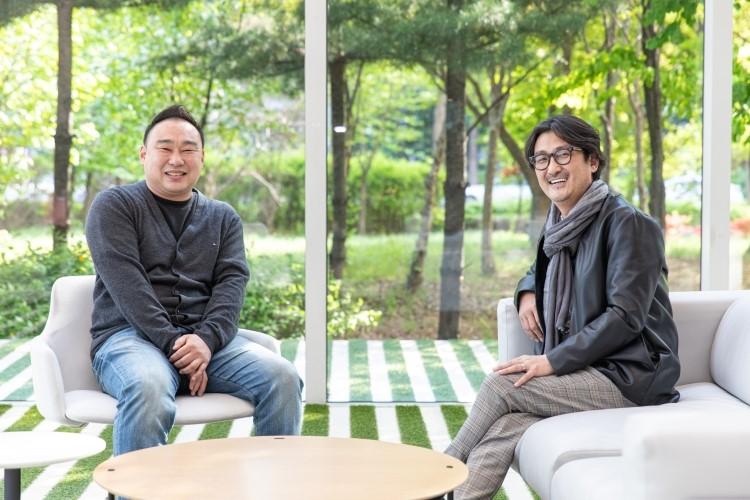 지식 큐레이팅 채널 '사피엔스 스튜디오'를 만든 정민식 CP(좌), 김민수 PD(우)가 CJ ENM 상암 본사 로비에 마련된 의자에 앉아 카메라를 향해 미소를 짓고 있다.