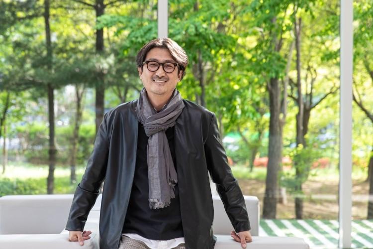 지식 큐레이팅 채널 '사피엔스 스튜디오'를 만든 정민식 CP가 CJ ENM 상암 본사 로비에 마련된 의자에 걸터 앉아 카메라를 향해 미소를 짓고 있다.