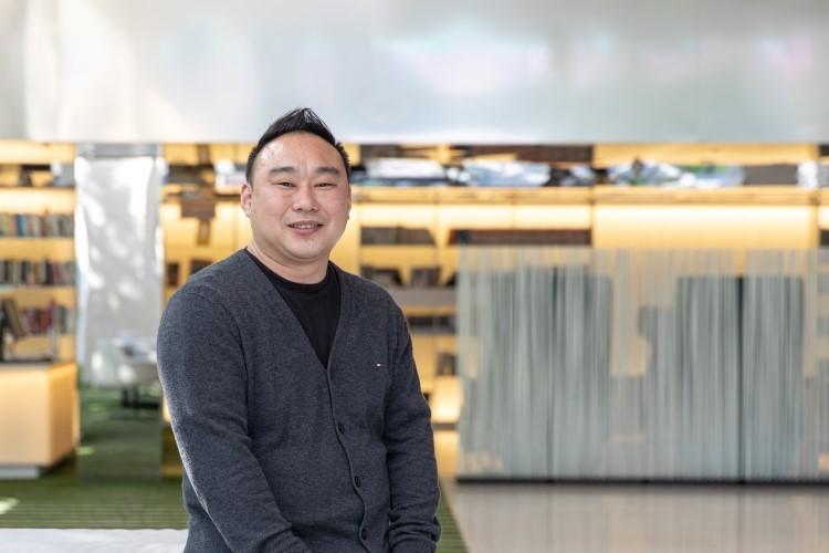 지식 큐레이팅 채널 '사피엔스 스튜디오'를 만든 김민식 PD가 CJ ENM 상암 본사 로비에서 카메라를 향해 포즈를 취하고 있다.