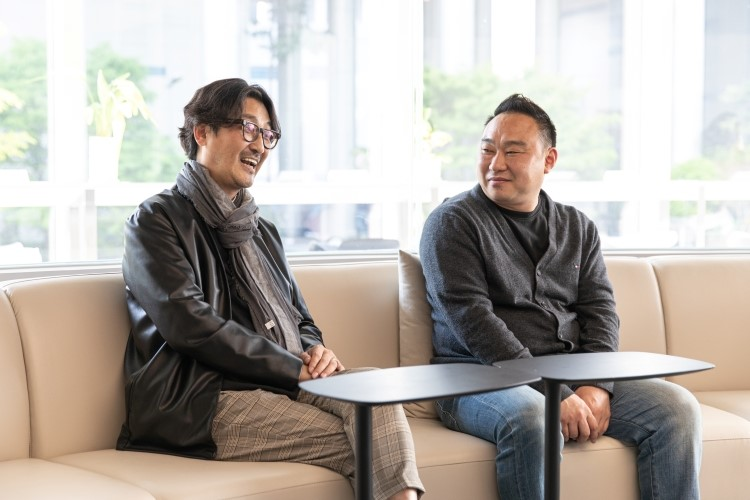 지식 큐레이팅 채널 '사피엔스 스튜디오'를 만든 정민식 CP(좌)가 테이블에 앉아 인터뷰에 응하고 있고, 김민수 PD(우)가 이를 쳐다보고 있다.