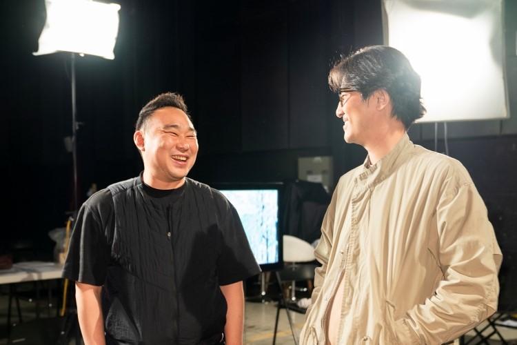 지식 큐레이팅 채널 '사피엔스 스튜디오'를 만든 정민식 CP(우)가 김민수 PD(좌)가 조명이 켜진 녹화 스튜디오 장에서 서로를 쳐다보며 미소를 짓고 있다.