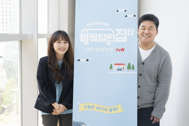 tvN '바퀴 달린 집 2' 강궁(우), 송명진(좌) PD가 프로그램 스탠드 배너를 사이에 두고 카메라를 향해 포즈를 취하고 있다.