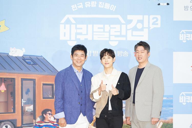 tvN '바퀴 달린 집 2'의 호스트인 (왼쪽부터) 성동일, 임시완, 김희원이 프로그램 포토월에 서서 카메라를 향해 포즈를 취하고 있다. 특히 새롭게 투입된 임시완은 쌍엄지를 치켜올리며 미소를 짓고 있다.
