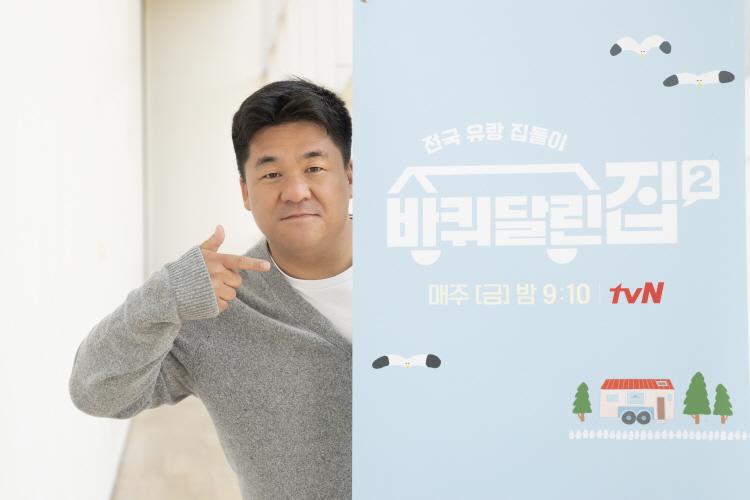 tvN '바퀴 달린 집 2' 강궁 PD가 프로그램 스탠드 배너를 가리키며 카메라를 향해 포즈를 취하고 있다.
