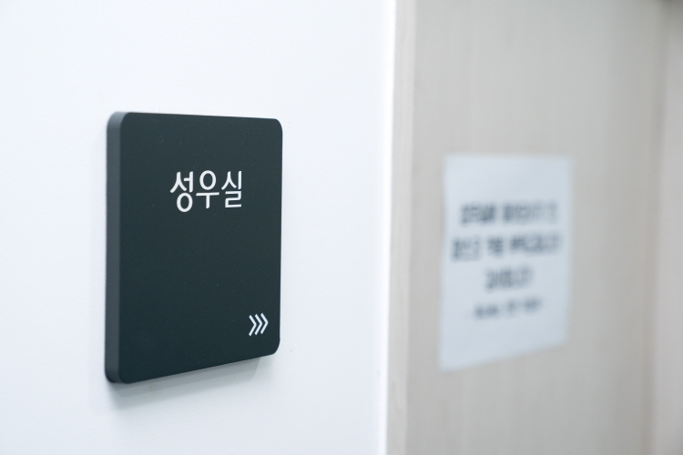 투니버스 성우실 입구 모습으로 성우실 문 왼쪽에 녹색 바탕으로 '성우실'이란 간판이 붙여져 있다.