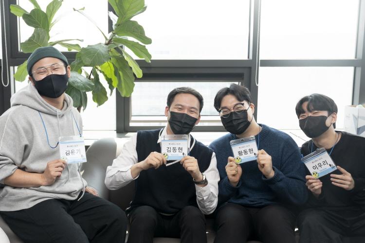 휴식을 책임지는 소파에서 활짝 웃으며 포즈를 취하는 투니버스 11기 전속 성우의 모습으로, (왼쪽부터)김윤기, 김동현, 황동현, 이우리 성우가 모두 목에 걸은 이름표를 들고 미소를 짓고 있다.