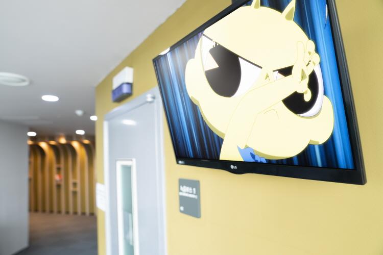 투니버스 녹음실 문 오른쪽 노란색 벽에 걸린 TV를 통해 신비아파트의 신비가 보여지고 있다.