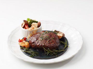 '스모키돔 채끝 스테이크'가 접시에 담긴 모습으로, 훈연한 스테이크에 로즈마리와 마늘, 버섯이, 다채로운 야채가 담겨있는 사이드 그릇이 놓여져 있다.