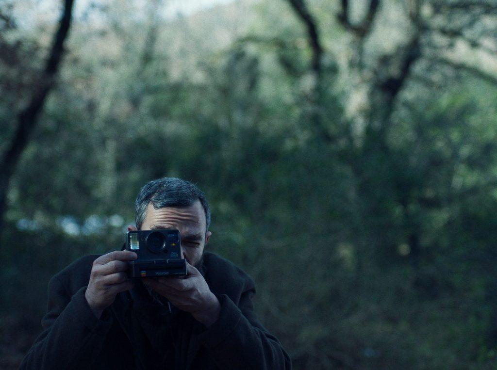 크리스토스 니코우 감독의 첫 장편 영화 '애플'의 한 장면으로 주인공 알리스가 숲을 등지고 폴라로이드 사진기로 누군가를 찍어주고 있다.