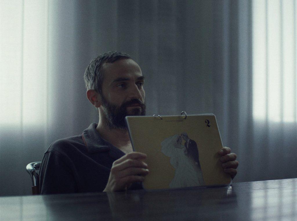 크리스토스 니코우 감독의 첫 장편 영화 '애플'의 한 장면으로 주인공 알리스가 의자에 앉아 결혼을 의미하는 그림을 들고 누군가를 응시하고 있다.