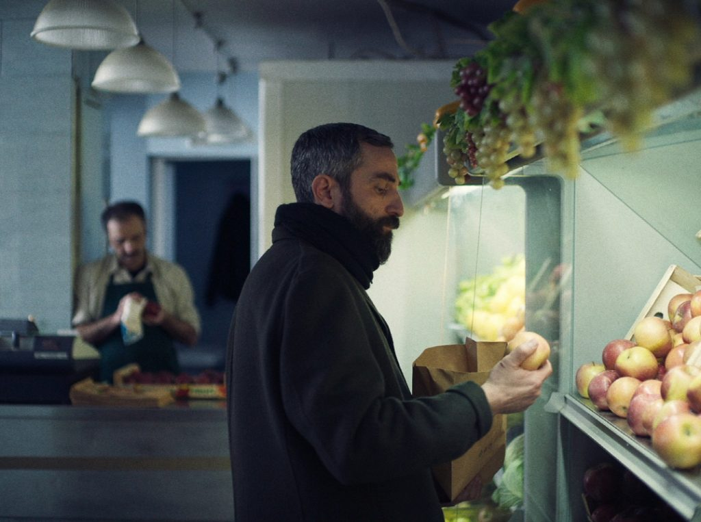 크리스토스 니코우 감독의 첫 장편 영화 '애플'의 한 장면으로 주인공 알리스가 식료품 가게에서 사과를 들고 고심하고 있는 모습이다.