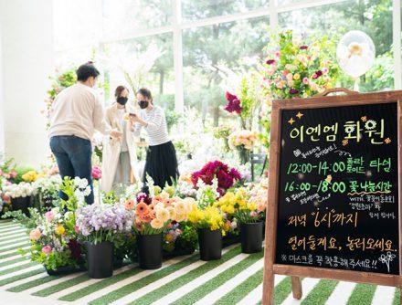 CJ ENM 1층 로비에 '이엔엠 화원'이란 이름으로 다양한 꽃을 가져다 놓았고, 사람들이 그 안에서 대화를 나누며 사진을 찍고 있다. 화원 앞에는 '이엔앰 화원'이라는 제목의 판넬이 설치되어 있고, 이용 시간이 적혀있다.