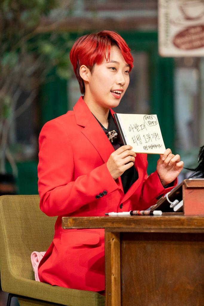 붉은색 옷을 입은 연반인 재재가 의자에 앉아 '아받대 티빙 1위 기원'이라는 센스 넘치는 문구를 어필하고 있는 모습이다.